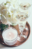 Wedding home decor. Bouquet of white flowers in a vase, candles and champagne on a copper tray vintage, wedding home decor stock photo