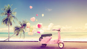 Wedding honeymoon. Classic motorcycle with heart balloon on beach blue sky concept of love in summer and wedding honeymoon - vintage color effect Stock Photos