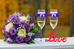 Wedding installation with wooden sign Love. Wedding installation with bridal bouquet, two decorated glasses and red wooden sign Love stock photo