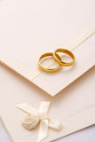 Wedding invitation. And two golden rings Royalty Free Stock Photo