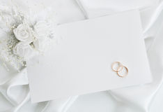The wedding invitation. With wedding rings and a bouquet of the bride on a white background Royalty Free Stock Photo