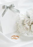 The wedding invitation. With wedding rings and a bouquet of the bride on a white background Stock Images