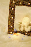Cherub Watching Over the Wedding Bands. Cream colored cherub looking out of a golden picture frame at two gold wedding bands  this is all on a cream colored silk Stock Photo