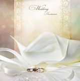 Wedding invitation. Card with calla lilies and golden rings Royalty Free Stock Images
