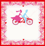 Wedding invitation with bride and groom riding tandem bicycle Royalty Free Stock Images