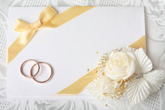 Wedding invitation card. With gold rings and satin rose Stock Photos
