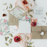 Wedding invitation cards, craft envelopes, pink and red roses and green leaves on white background Royalty Free Stock Photo