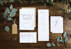 Wedding Invitation Cards Papers Laying on Table Decorate With Le. Aves stock photo