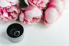 Wedding rings, envelope, peonies flowers on white background, copy space. Wedding invitation concept - rings, envelope, pink peonies flowers on white background royalty free stock photo