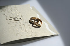 Wedding invitation and rings Stock Photos