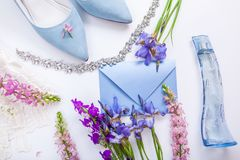 Wedding invitation surrounded with flowers, bride`s shoes, perfume and jewellery. Morning of bride. Wedding invitation surrounded with flowers, blue bride`s stock photos