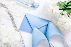 Wedding invitation surrounded with flowers, bride`s shoes and jewellery. Morning of bride. Wedding invitation surrounded with peonies flowers, bride`s blue shoes stock photos
