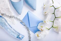 Wedding invitation surrounded with flowers, bride`s shoes and jewellery. Morning of bride. Wedding invitation surrounded with white orchid flowers, bride`s blue royalty free stock images