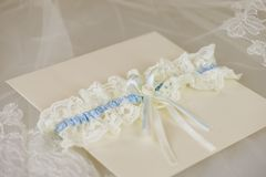 Wedding invitation with a wedding garter. Creamy wedding invitation with a blue and white wedding garter resting on ebroidered lace Stock Image