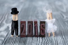 Wedding invitation. 2016 year. Groom in black suit and bride in white dress. Clothespins Royalty Free Stock Image
