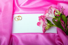Wedding invite blank. Wedding invitation with flowers and rings surrounded by pink silk Stock Photography