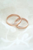 Wedding invite with rose gold rings Stock Image