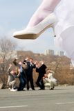 Wedding joke. The huge heel of the bride hangs above bridegroom with friends Stock Photography