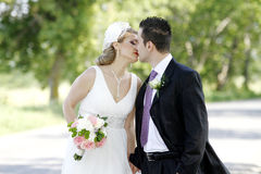 Wedding kiss. Bride and groom kissing outdoors royalty free stock photos