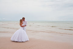 Wedding kiss. On a beach. Newly married after beach wedding ceremony royalty free stock image