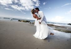Wedding kiss. As husband and wife shot on the beach of a resort.  Horizontal orientation, slight blur filter used on the clouds Royalty Free Stock Photo