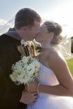 Wedding kiss. A bride and groom kissing under a veil outdoors Stock Photos