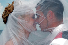 Wedding kiss. A couple about to kiss under a veil outdoors by the sea stock photography