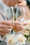 Wedding kiss. Wedding glasses with champagne over kissing bride and groom stock image
