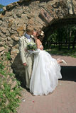 Wedding kiss. Bride and bridegroom are kissed beside bridge in park Royalty Free Stock Image