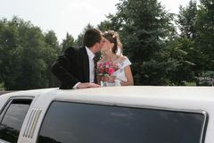 Wedding kiss. Bridegroom and bride are kissed in limousine Stock Images