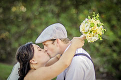 Wedding kiss. A bride and groom kissing in a park Stock Photography