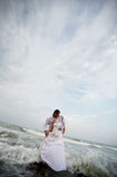 Wedding kiss (bride and groom portrait). Beautiful newlyweds couple kissing in a stormy sea setup stock photo