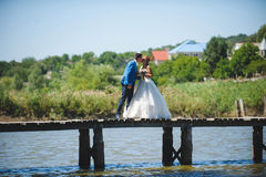 Wedding Kiss on Bridge. Groom kissing bride on bridge Royalty Free Stock Photo