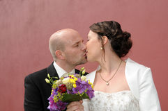 Wedding kiss. Groom gives a tender kiss to his wife Royalty Free Stock Photo