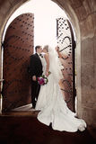 Wedding kiss. A groom kissing his bride in front of an open old castle door. Formal wedding