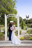 Wedding kiss. A military groom in uniform kissing his bride under an arch in a park Stock Photo