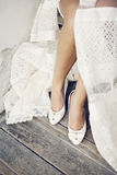 Wedding legs. Female dressed in a wedding dress legs isolated Stock Image