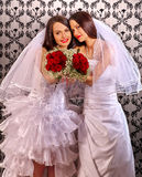 Wedding lesbians girl in bridal dress. Happy lesbians newlyweds keeps roses bouquet Royalty Free Stock Image