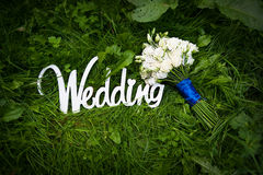 Wedding letters with white flowers on grass.  Royalty Free Stock Photography