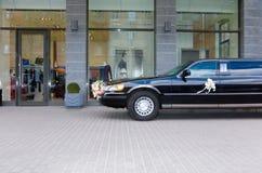 Wedding limousine near the shop. Wedding black limousine near the shop Royalty Free Stock Photo
