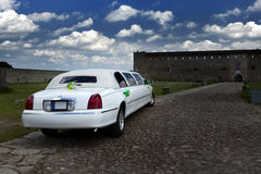 Wedding limousine in the yard of fortress Narva, Estonia - a traditional place of wedding ceremonies of citizens. Stock Photos