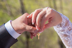 Wedding lock with hands. Wedding lock key`s in newlyweds hands, closeup Royalty Free Stock Photography