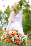 Wedding, look on each other. Wedding bouquet with bride and groom in background Stock Photography