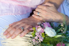 Wedding love. Just married moment with groom and bride hands with wedding rings and flowers Stock Photos