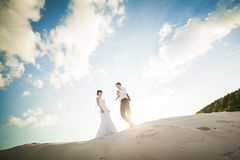 Wedding love couple running on the sand. Bride and Groom Royalty Free Stock Photo