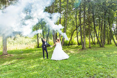 Wedding, love, relationships, marriage. Smiling bride and groom with blue smoke. Wedding, love, relationships, marriage. Smiling bride and groom dancing in blue Stock Images
