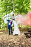 Wedding, love, relationships, marriage. Smiling newlyweds and colored smoke Stock Photography