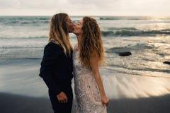 Wedding lovestory, как раз пожененная пара около океана на заходе солнца Стоковое Изображение