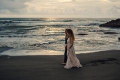 Wedding lovestory, как раз пожененная пара около океана на заходе солнца Стоковая Фотография