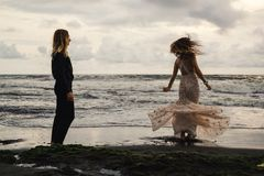 Wedding lovestory, как раз пожененная пара около океана на заходе солнца Стоковые Изображения